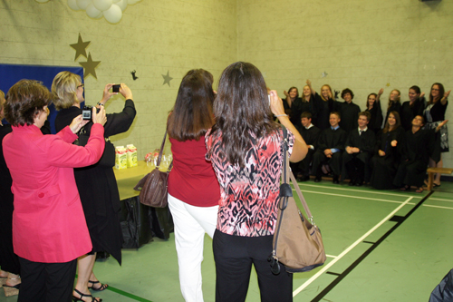 Women taking pictures of graduating students posing